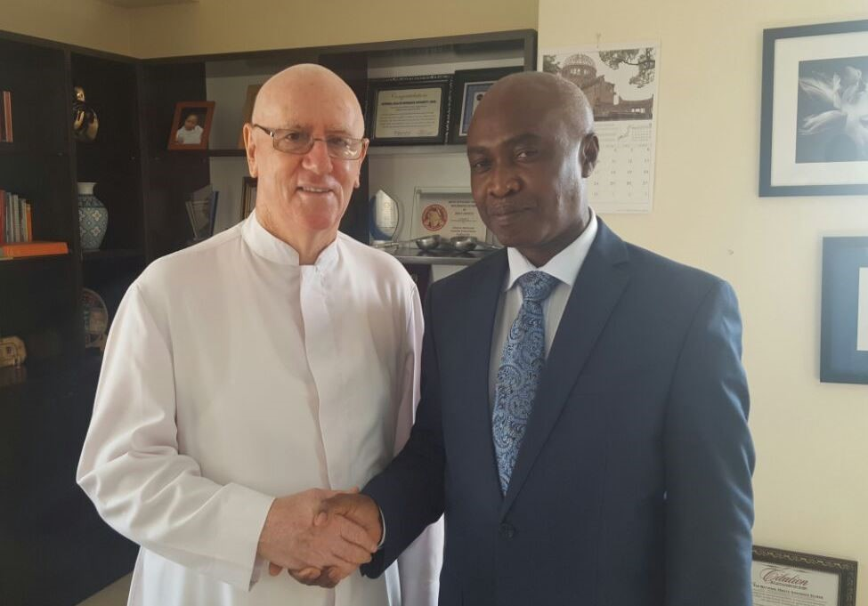 Rev Father Andrew Campbell (L) in a handshake with NHIS boss, Nathaniel Otoo (R)