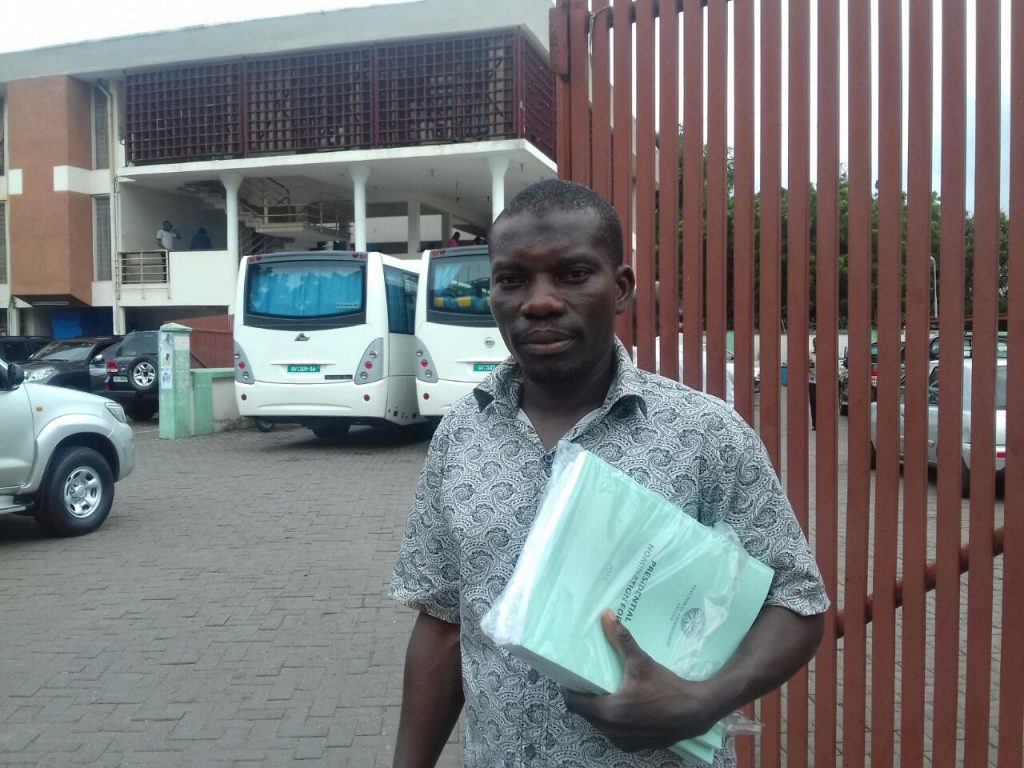 Deputy National Youth Organiser for the NDC, Jibril Mahdi holding nomination forms for candidate John Mahama